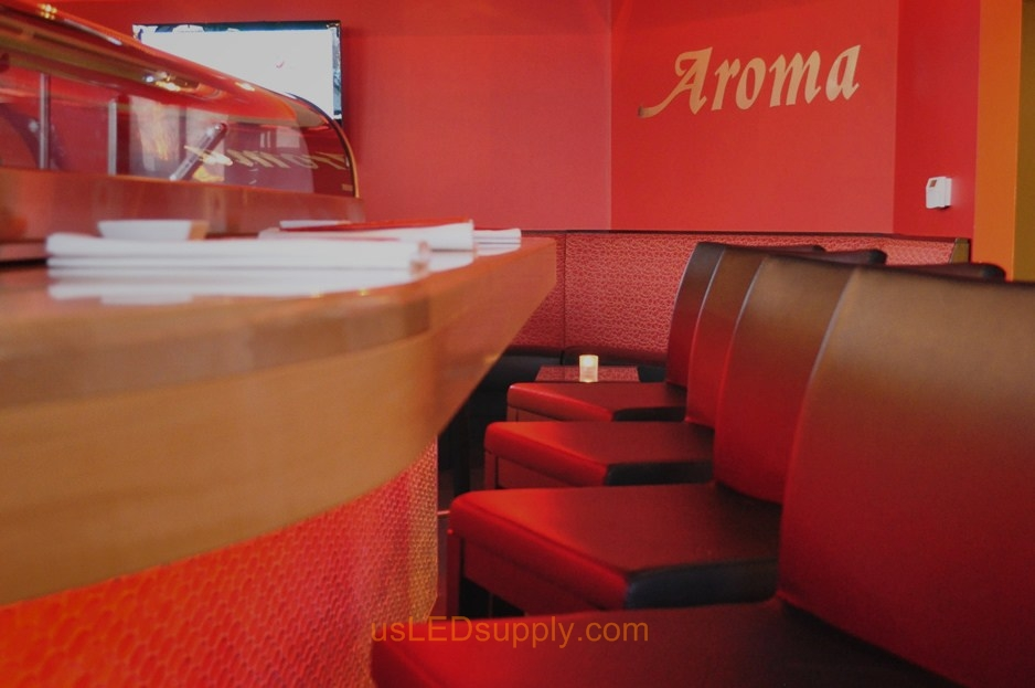Aroma Cafe under bar lighting falls upon stools.