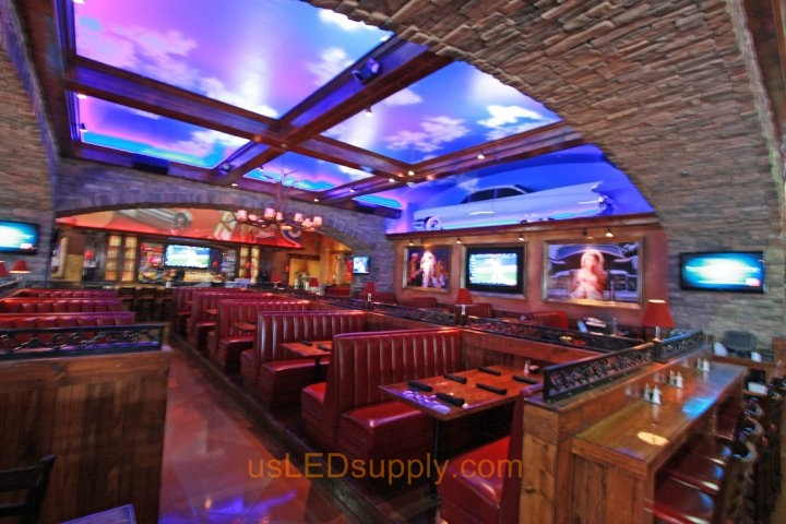 White LED strips light up the cloudy blue sky ceilings in this country restaurant.