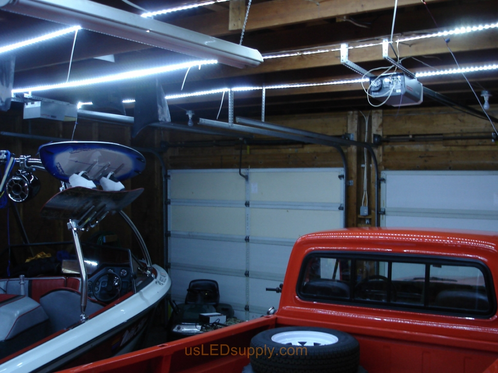 Garage with cool white flexible LED strips installed across beams.