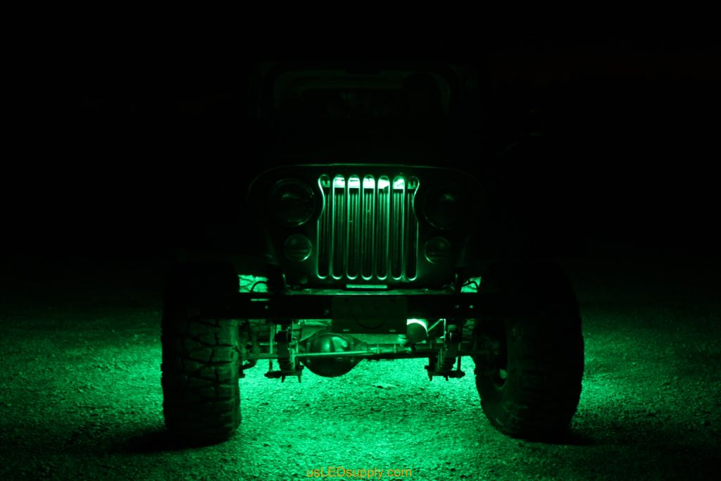 Green LEDs light up the grill on the front of a Jeep.