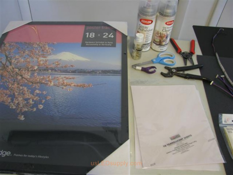 Poster frame, scissors, adhesive, transluscent paper for making LED silhouette art project.