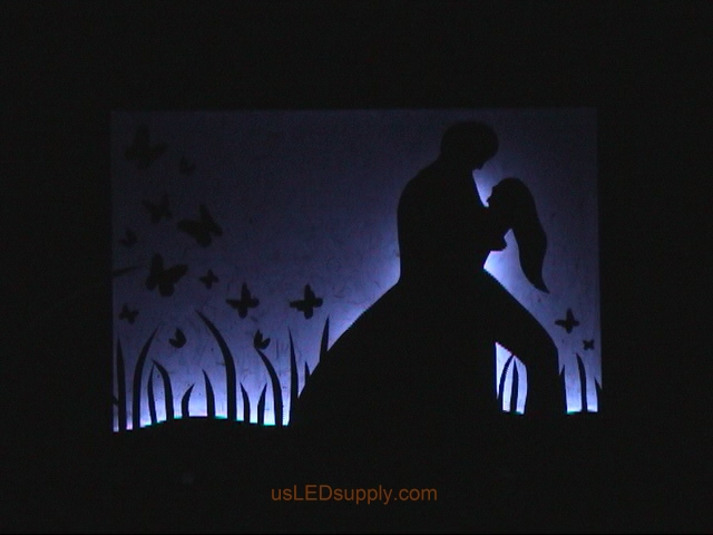 RGB LED silhouette art project with couple in love set on blue color.