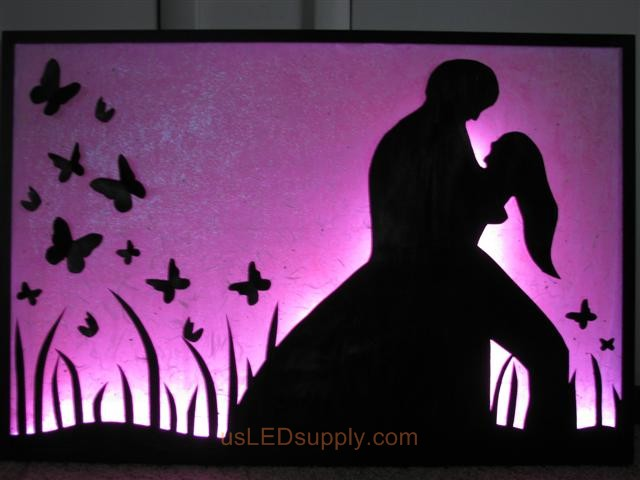RGB LED silhouette art project with couple in love set on pink color.