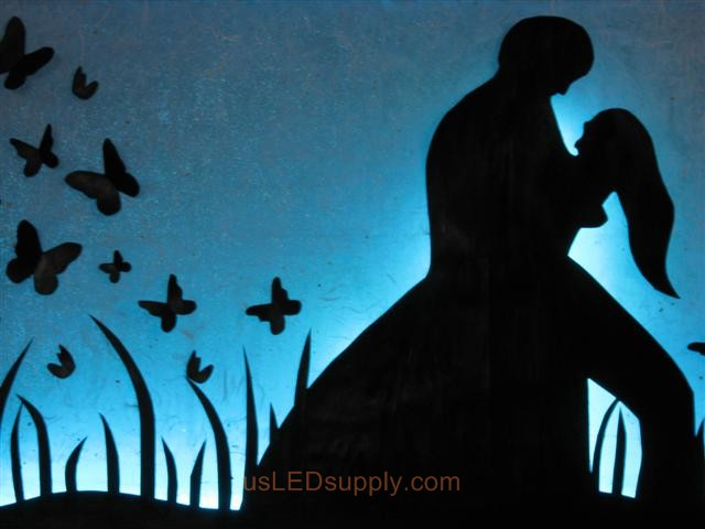RGB LED silhouette art project with couple in love set on light blue color.