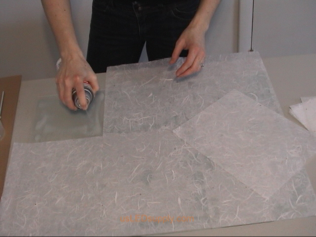 Use spray adhesive or gluestick to attach transluscent paper to glass.