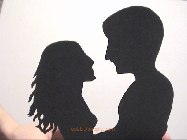 Couple heads cut out of black poster paper.