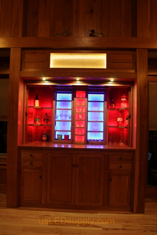 RGB LED Strips illuminate the shelves of this home bar.