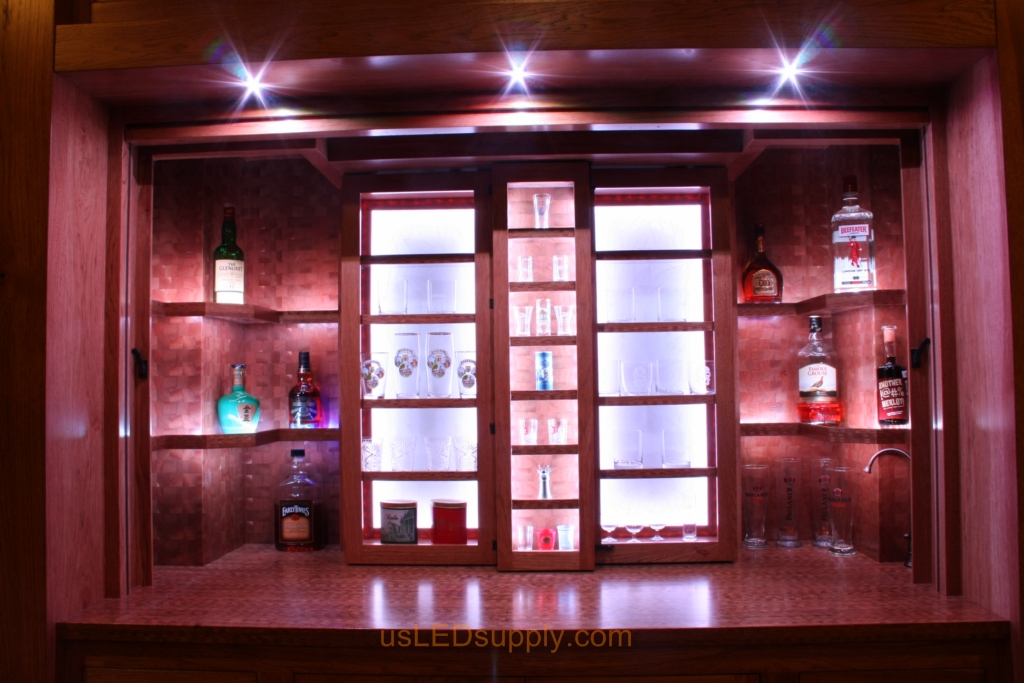 The cabinets open up to reveal the bar with shelves holding liquer bottles and glasses.