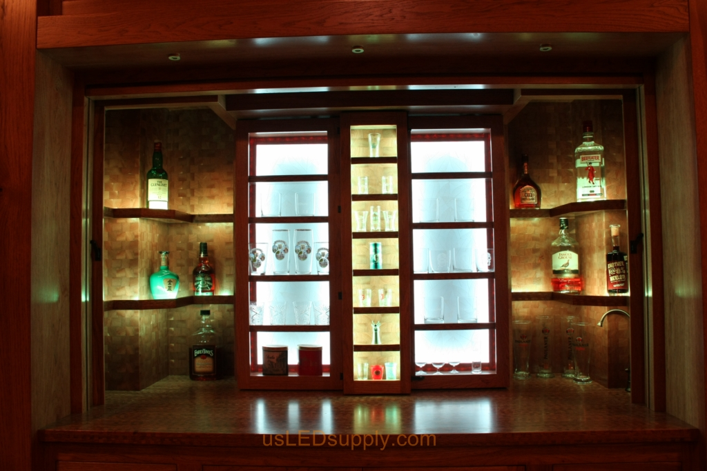 RGB LED Strips in different zones create color effects on this home bar shelving.