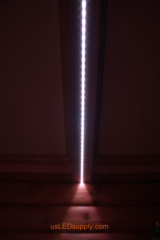 Close up of LED strip running along the beam in a log cabin living room.