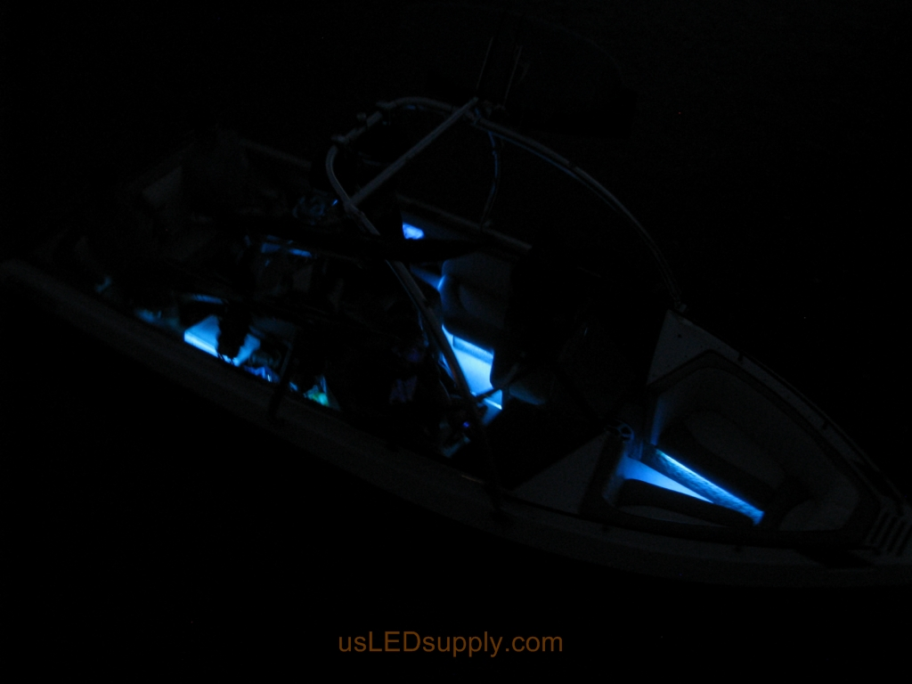 Malibu Sunsetter on the water at night with RGB color changing LEDs lighting up the interior.