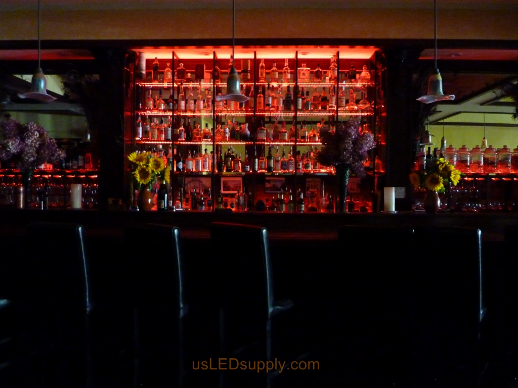 Glass shelving in bar with RGB flexible LED strips behind them makes the glass shelving and bottles glow.