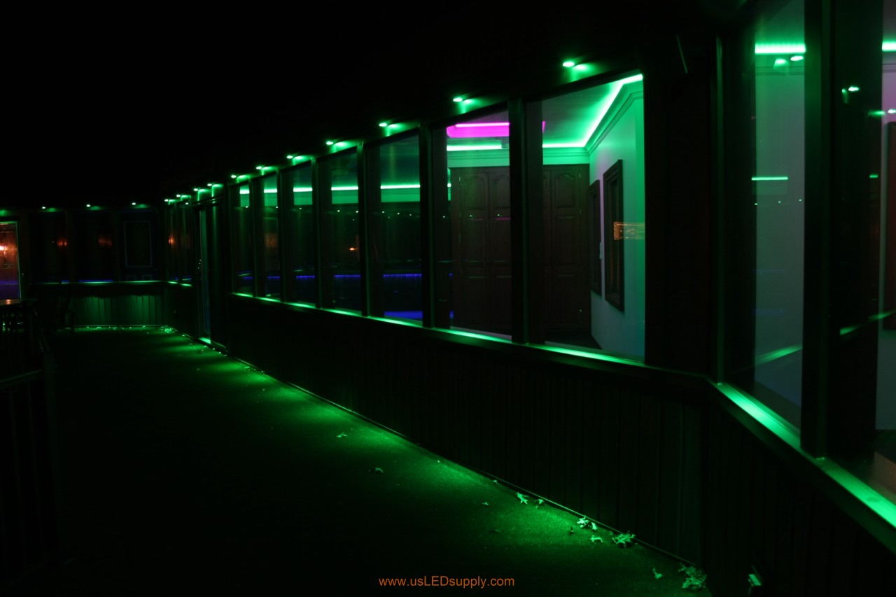 RGB LED puck lights above windows of a glassed in walkway.