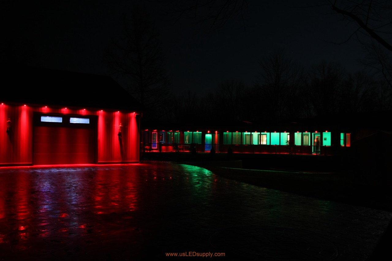 RGB Puck Lights outside of a garage and above enclosed glass walkway windows.