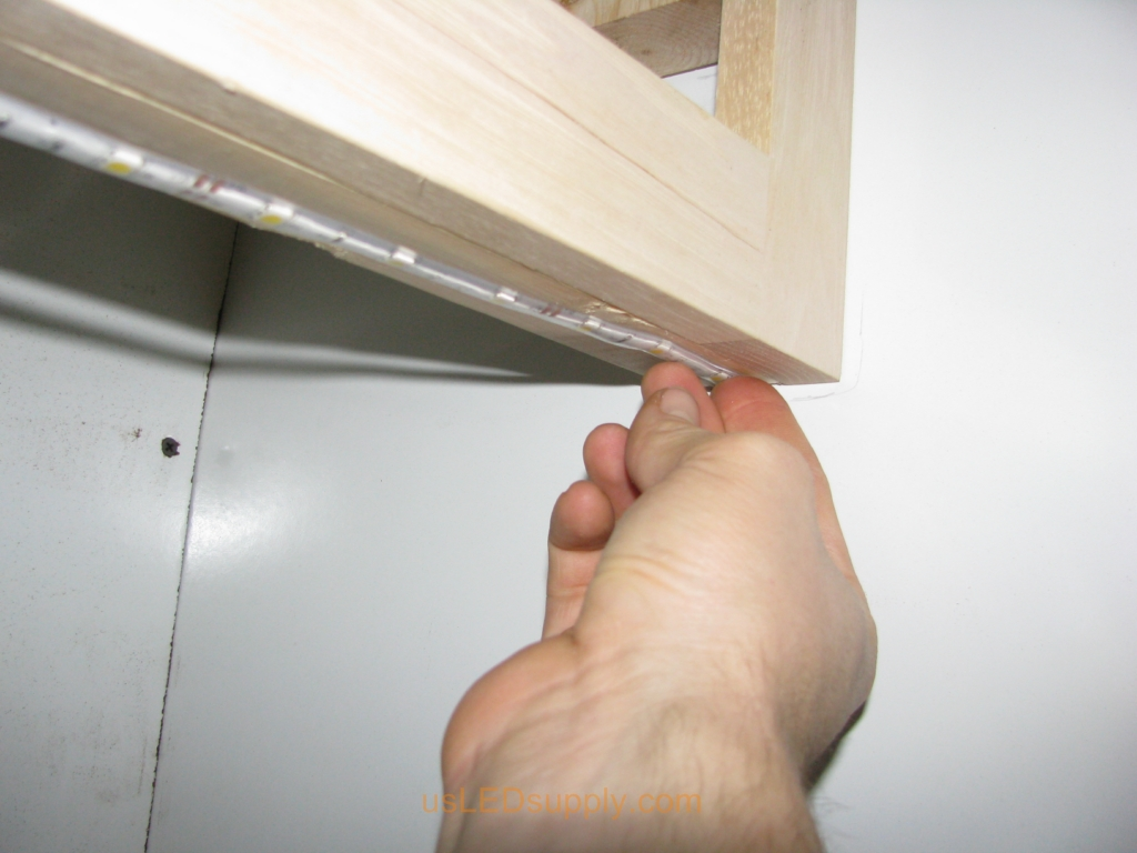 Attaching the flexible LED strip to the bottom of the cabinet using SMD self stick backing.