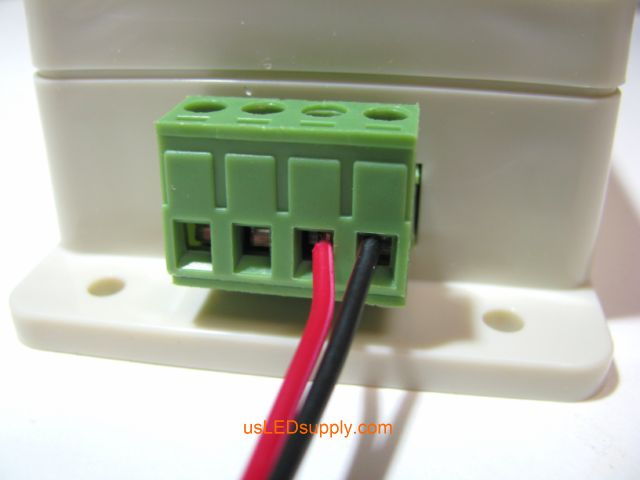 Red and black wires inserted into the terminal block in the correct order, red for positive power output and black for negative power output